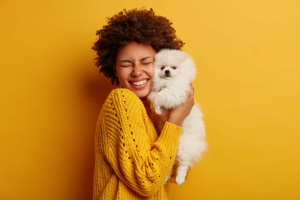 smiling woman holding small white dog