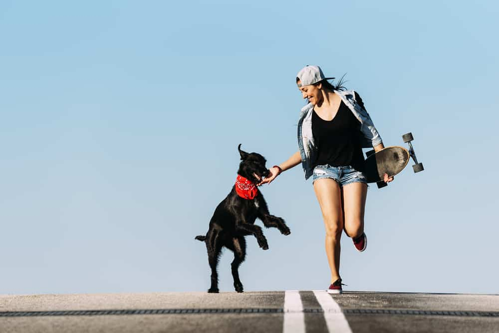 skater woman with black dog red bandana