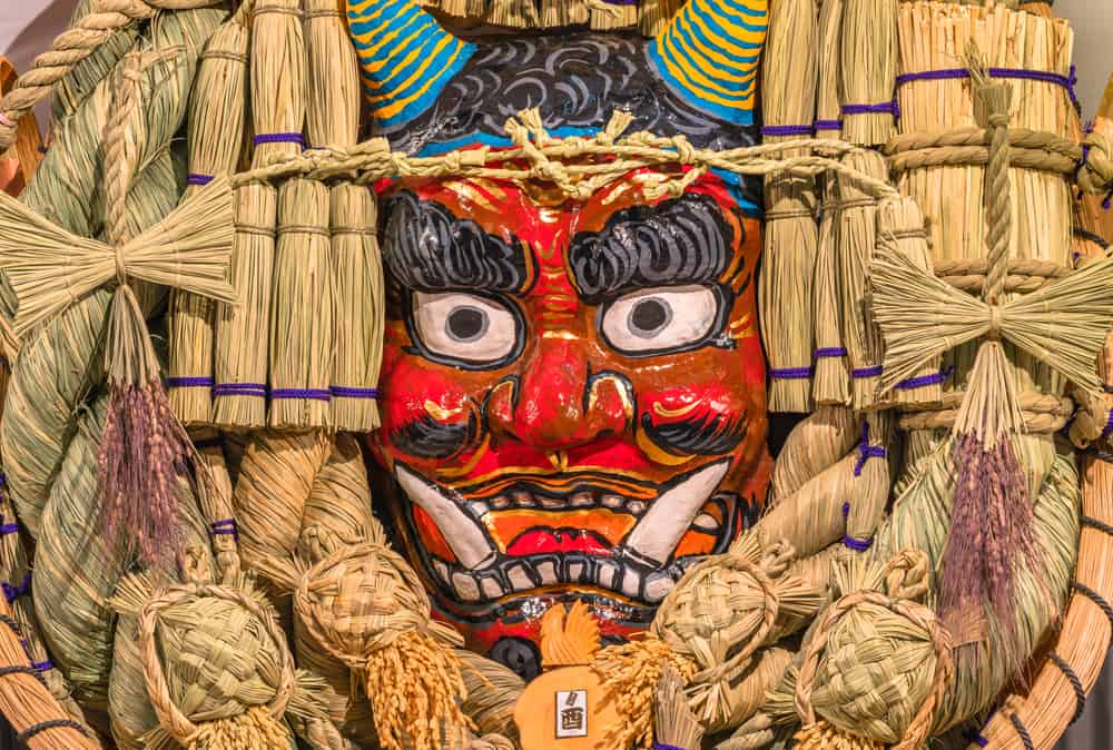 japanese demon mask surrounded by straw